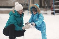 Οικογενειακός sculpts χιονάνθρωπος Στοκ Εικόνες