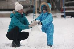 Οικογενειακός sculpts χιονάνθρωπος Στοκ εικόνες με δικαίωμα ελεύθερης χρήσης