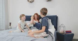 Οικογενειακό ευτυχές χαμόγελο που βρίσκεται στο κρεβάτι στην κρεβατοκάμαρα, εύθυμοι γονείς με τα παιδιά στο χρόνο εξόδων πρωινού  απόθεμα βίντεο