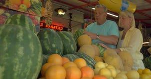 Οικογενειακό ζεύγος που επιλέγει το καρπούζι στην αγορά οδών απόθεμα βίντεο