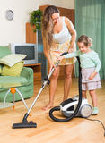 Οικογενειακό καθαρίζοντας σπίτι με την ηλεκτρική σκούπα Στοκ φωτογραφία με δικαίωμα ελεύθερης χρήσης