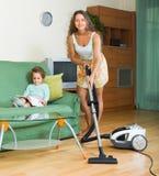 Οικογενειακό καθαρίζοντας σπίτι με την ηλεκτρική σκούπα Στοκ Φωτογραφίες