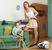 Οικογενειακό καθαρίζοντας σπίτι με την ηλεκτρική σκούπα Στοκ Φωτογραφία