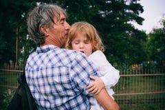 Οικογενειακό κορίτσι στα όπλα του πατέρα του υπαίθρια Στοκ Εικόνες