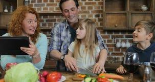 Οικογενειακό μαγείρεμα μαζί στην κουζίνα που χρησιμοποιεί τη συνταγή από τους γονείς ψηφιακών υπολογιστών ταμπλετών με δύο παιδιά φιλμ μικρού μήκους