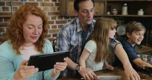 Οικογενειακό μαγείρεμα μαζί στην κουζίνα που χρησιμοποιεί τη συνταγή από τους γονείς ψηφιακών υπολογιστών ταμπλετών με δύο παιδιά απόθεμα βίντεο