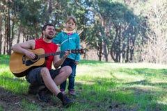 Οικογενειακό ντουέτο: Μπαμπάς που παίζει την κιθάρα με την κόρη του, ελεύθερου χώρου για το κείμενό σας Στοκ φωτογραφίες με δικαίωμα ελεύθερης χρήσης