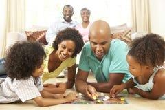 Οικογενειακό παίζοντας επιτραπέζιο παιχνίδι στο σπίτι Στοκ Εικόνες