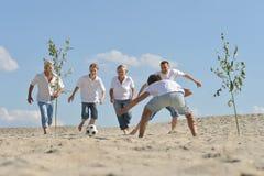 Οικογενειακό παίζοντας ποδόσφαιρο σε μια παραλία στη θερινή ημέρα στοκ εικόνες