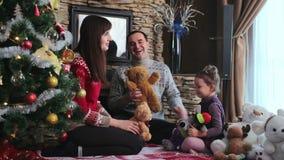 Οικογενειακό παιχνίδι με την κόρη τους κοντά στο χριστουγεννιάτικο δέντρο απόθεμα βίντεο