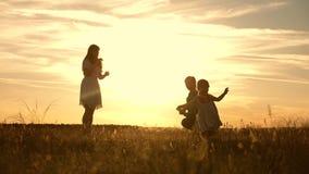 Οικογενειακό παιχνίδι με την κόρη τους στις ακτίνες του ήλιου το μωρό πηγαίνει από τον μπαμπά στο mom και γελά o mom και μπαμπάς απόθεμα βίντεο