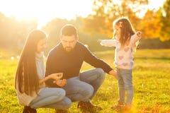 Οικογενειακό παιχνίδι στο πάρκο φθινοπώρου που έχει τη διασκέδαση στο ηλιοβασίλεμα Στοκ εικόνα με δικαίωμα ελεύθερης χρήσης