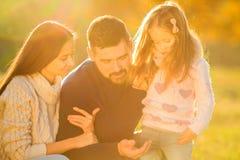 Οικογενειακό παιχνίδι στο πάρκο φθινοπώρου που έχει τη διασκέδαση Στοκ Εικόνες