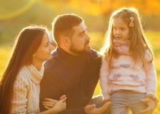 Οικογενειακό παιχνίδι στο πάρκο φθινοπώρου που έχει τη διασκέδαση στο ηλιοβασίλεμα Στοκ Εικόνες