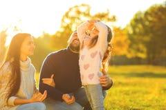 Οικογενειακό παιχνίδι στο πάρκο φθινοπώρου που έχει το ηλιοβασίλεμα διασκέδασης τ Στοκ φωτογραφίες με δικαίωμα ελεύθερης χρήσης