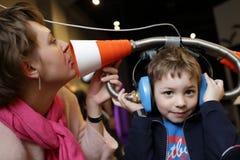 Οικογενειακό παιχνίδι με τα μεγάλα ακουστικά παιχνιδιών Στοκ Εικόνες