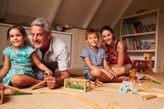Οικογενειακό παιχνίδι με τα παιχνίδια σε έναν αττικό χώρο για παιχνίδη, πορτρέτο Στοκ φωτογραφίες με δικαίωμα ελεύθερης χρήσης