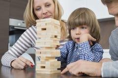Οικογενειακό παιχνίδι με τους ξύλινους φραγμούς στο σπίτι Στοκ Φωτογραφίες