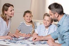 Οικογενειακό παιχνίδι με το γρίφο στον πίνακα στο σπίτι από κοινού Στοκ Εικόνες