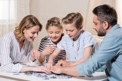 Οικογενειακό παιχνίδι με το γρίφο στον πίνακα στο σπίτι από κοινού Στοκ εικόνα με δικαίωμα ελεύθερης χρήσης