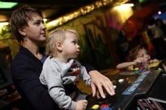 Οικογενειακό παιχνίδι στα μηχανήματα τυχερών παιχνιδιών με κέρματα Στοκ Εικόνες