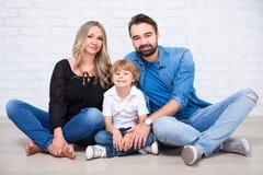 Οικογενειακό πορτρέτο πέρα από τον άσπρο τουβλότοιχο Στοκ Εικόνες