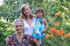 Οικογενειακό πορτρέτο σε έναν κήπο, τρεις γενεές Στοκ φωτογραφία με δικαίωμα ελεύθερης χρήσης