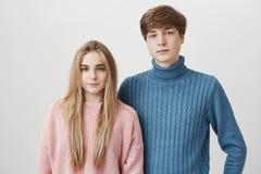 Οικογενειακό πορτρέτο του καυκάσιου νέου ζεύγους στα πουλόβερ Το ξανθομάλλη αγόρι και το κορίτσι με τα μπλε μάτια κοιτάζουν με τη Στοκ Εικόνα