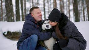 Οικογενειακό πορτρέτο του χαριτωμένου ευτυχούς ζεύγους που αγκαλιάζει με το από την Αλάσκα σκυλί malamute τους που γλείφει το ανθ φιλμ μικρού μήκους