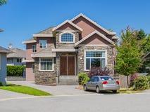 Οικογενειακό σπίτι πολυτέλειας με ένα αυτοκίνητο που σταθμεύουν driveway Κατοικημένο σπίτι την ηλιόλουστη ημέρα στο υπόβαθρο μπλε στοκ φωτογραφία