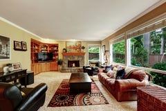 Οικογενειακό δωμάτιο πολυτέλειας με την άνετη τακτοποιημένη πέτρα εστία Στοκ Εικόνα