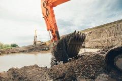 Οικοδομές εθνικών οδών με τη γη και το χώμα φόρτωσης σεσουλών εκσκαφέων Στοκ Φωτογραφία