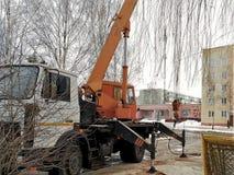 Οικοδομές επισκευής, διάτρυση του καλά αρθρωμένου εξοπλισμού στο τρακτέρ, που λειτουργούν, στα πλαίσια των σπιτιών, στοκ φωτογραφία με δικαίωμα ελεύθερης χρήσης