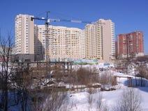 Οικοδόμηση ενός μεγάλου multi-storey κτηρίου σε ένα νέο κατοικημένο τέταρτο στην πόλη κοντά στα παλαιά ξύλινα σπίτια στο Novosibi στοκ εικόνες
