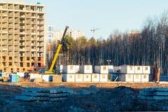 Οικοδόμηση ενός νέου multi-storey κτηρίου που περιβάλλεται από τα δάση Γερανοί κατασκευής ενάντια στο μπλε ουρανό στοκ εικόνες