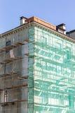 Οικοδόμηση κάτω από την ανακαίνιση με τα υλικά σκαλωσιάς και την πράσινη αλιεία με δίχτυα Στοκ εικόνες με δικαίωμα ελεύθερης χρήσης