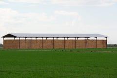 Οικοδόμηση με τα δέματα του σανού που περιβάλλονται από τους πράσινους τομείς στοκ φωτογραφία με δικαίωμα ελεύθερης χρήσης