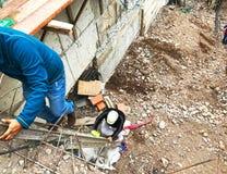 Οικοδόμοι που αναρριχούνται στη σκάλα στο εργοτάξιο οικοδομής Τσιμέντο και βράχοι στοκ εικόνα