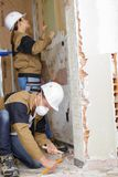 Οικοδόμοι που χαράζουν το σπίτι τοίχων και πατωμάτων Στοκ Εικόνες