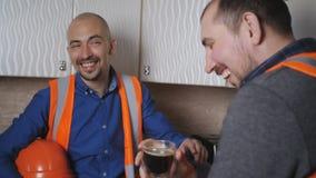 Οικοδόμοι στα λειτουργώντας ενδύματα και προστατευτικά κράνη, καφές κατανάλωσης στην κουζίνα κατά τη διάρκεια ενός σπασίματος απόθεμα βίντεο