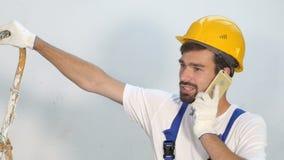 Οικοδόμος ή επόπτης στην περιοχή που χρησιμοποιεί το κινητό τηλέφωνο απόθεμα βίντεο