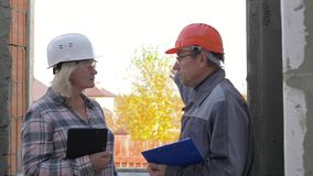Οικοδόμος και πελάτης σε ένα κράνος που συζητά το σχέδιο της κατασκευής του σπιτιού απόθεμα βίντεο