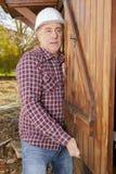 Οικοδόμος που εγκαθιστά την ξύλινη πόρτα υπαίθρια Στοκ Φωτογραφίες