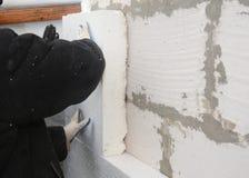 Οικοδόμος που εγκαθιστά τον άκαμπτο styrofoam πίνακα μόνωσης για την ενέργεια - αποταμίευση Άκαμπτη εξωθημένη μόνωση πολυστυρολίο στοκ εικόνα