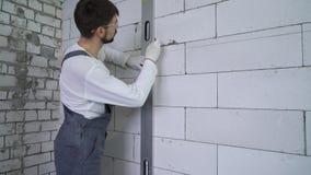 Οικοδόμος που επισύρει την προσοχή μια γραμμή στον τοίχο σύμφωνα με το επίπεδο ακτίνων λέιζερ φιλμ μικρού μήκους