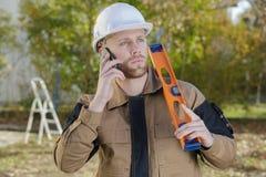Οικοδόμος που στέκεται στο εργοτάξιο που μιλά στο κινητό τηλέφωνο Στοκ Φωτογραφία