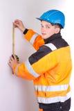 Οικοδόμος στα λειτουργώντας ενδύματα που μετρούν τον τοίχο Στοκ εικόνα με δικαίωμα ελεύθερης χρήσης