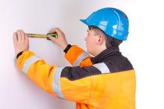 Οικοδόμος στα λειτουργώντας ενδύματα που μετρούν τον τοίχο Στοκ Φωτογραφία
