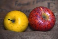 Οικολογικά ζωηρόχρωμα μήλα στο καφετί raffia ύφασμα Κίτρινος και κόκκινος Στοκ φωτογραφία με δικαίωμα ελεύθερης χρήσης