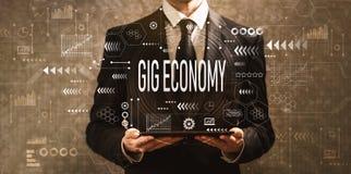 Οικονομία συναυλιών με τον επιχειρηματία που κρατά έναν υπολογιστή ταμπλετών απεικόνιση αποθεμάτων